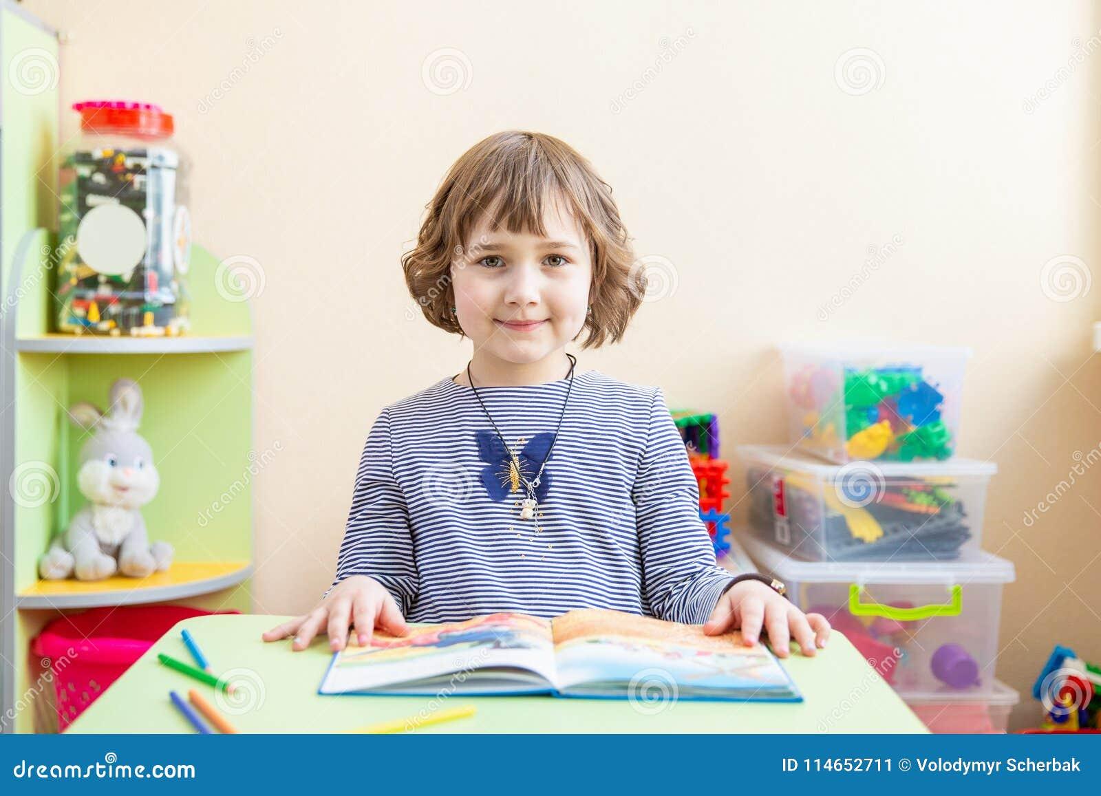 Nettes kleines Mädchen, das Hausarbeit, ein Buch, Färbungsseiten, ein Schreiben und eine Malerei lesend tut Kinderfarbe Kinderabg