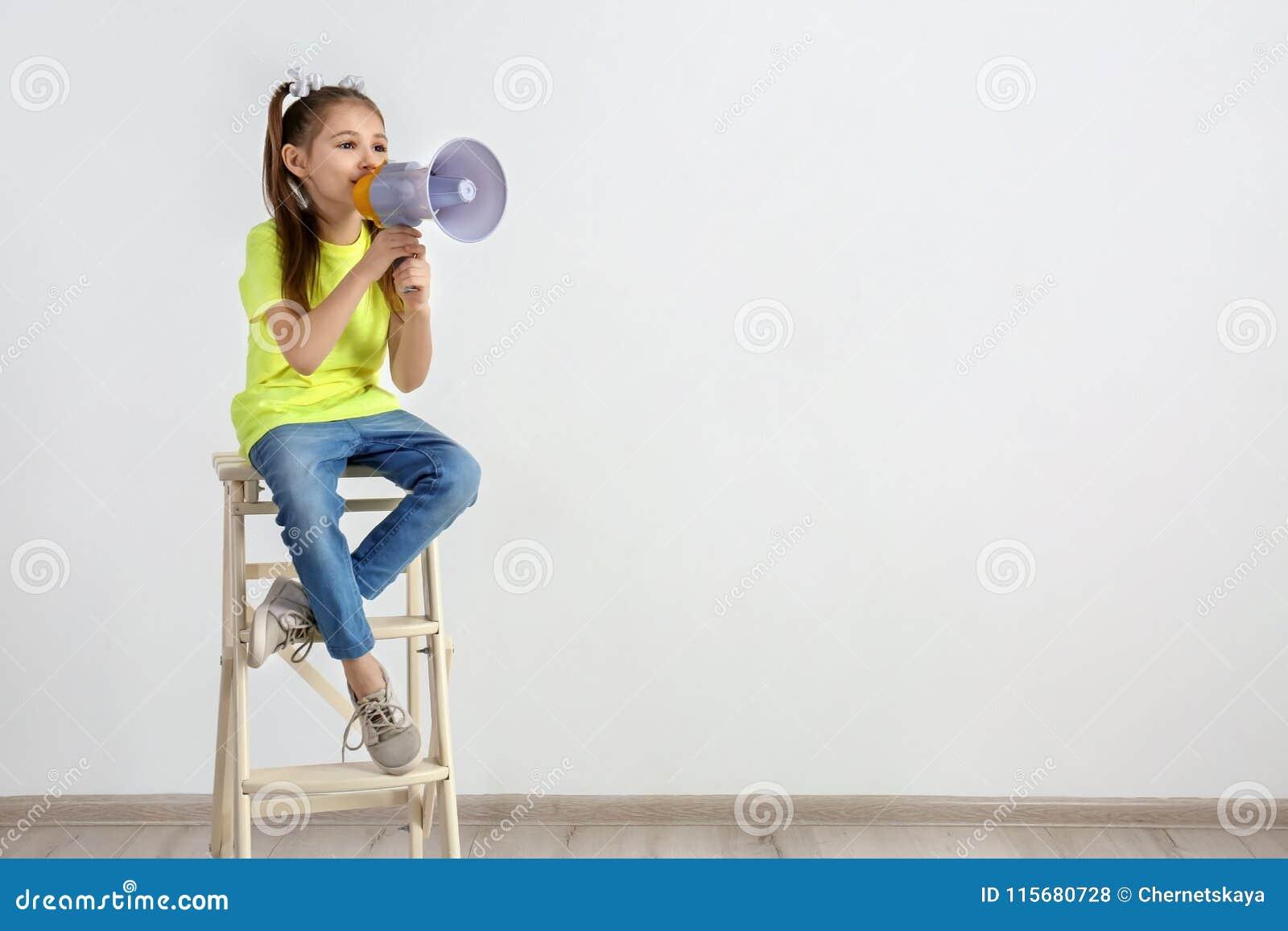 Nettes kleines Mädchen, das mit Megaphon sitzt