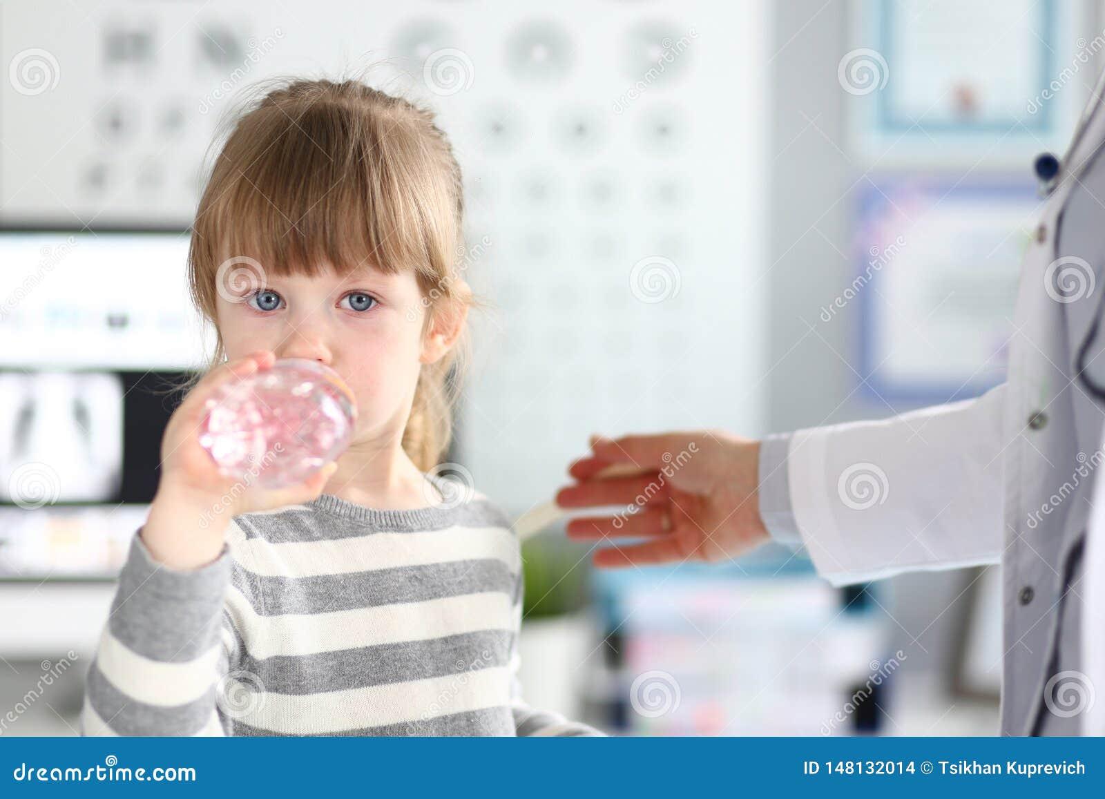Nettes kleines Mädchen, das Wasser in Doktorbüro erhält