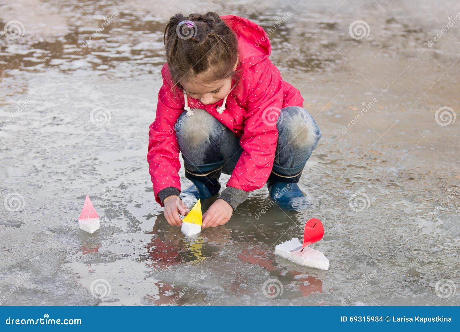 Nettes kleines Mädchen in den Regenstiefeln, die mit Schiffen wässern spielen im Frühjahr, Pfütze