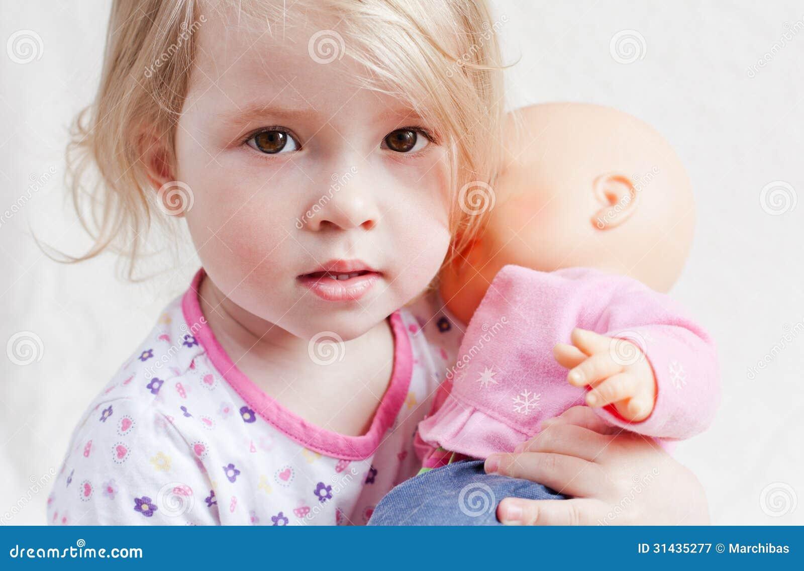 Nettes kleines Mädchen mit einer Puppe