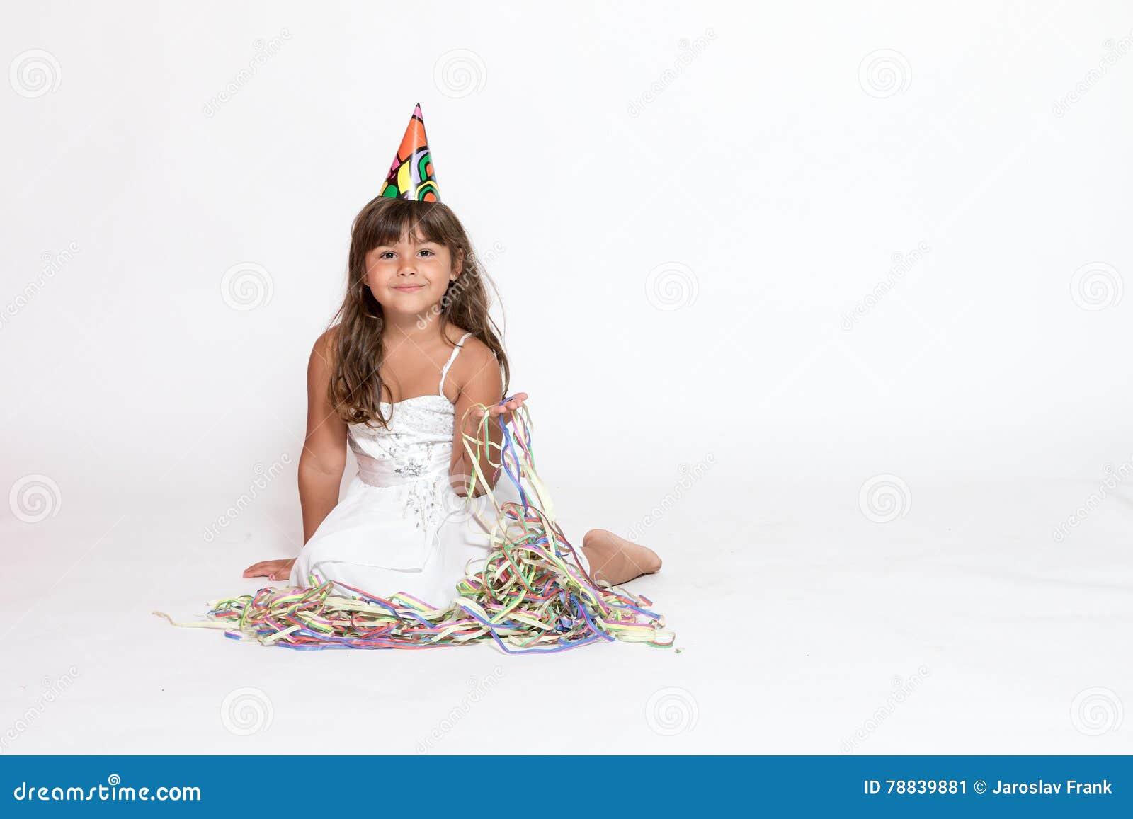 Nettes kleines Mädchen sitzt auf dem weißen Hintergrund