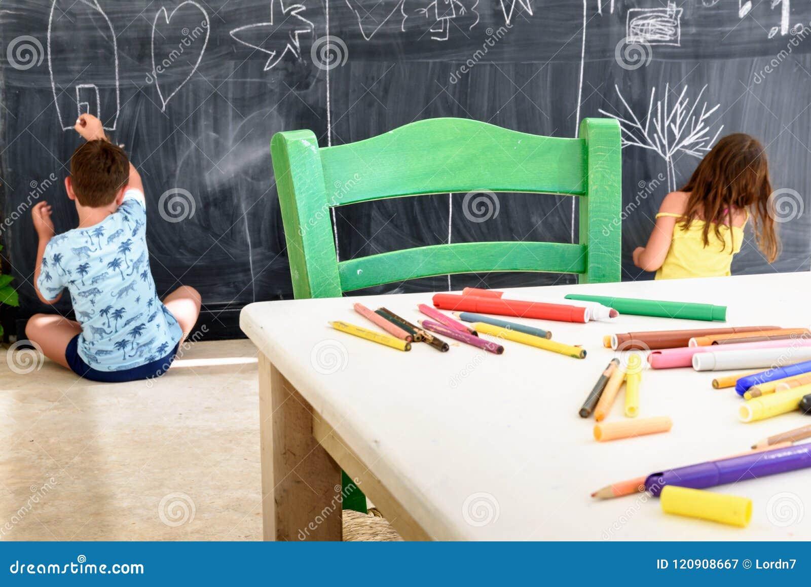 Nettes kleines Mädchen und Jungenzeichnung und -malerei am Kindergarten Kreativer Tätigkeitskinderverein