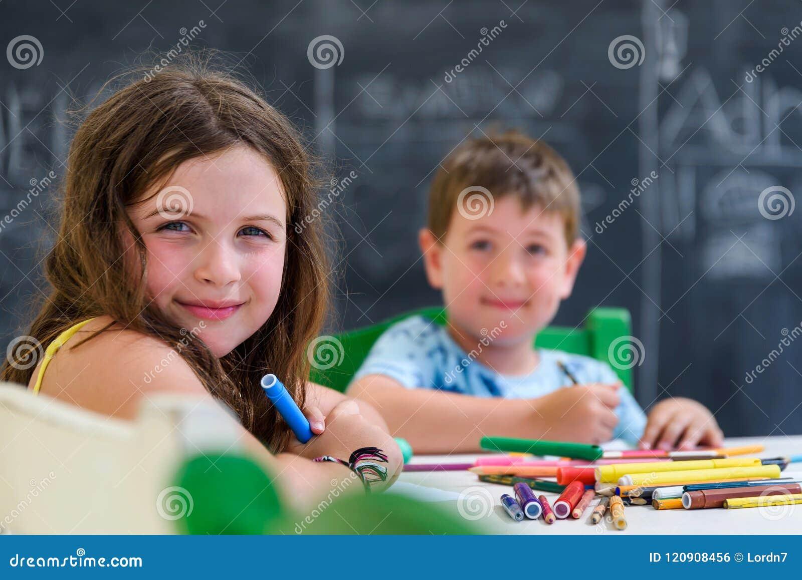 Nettes kleines Mädchen und Jungenzeichnung und -malerei mit bunten Markierungsstiften am Kindergarten Kreativer Tätigkeitskinderv