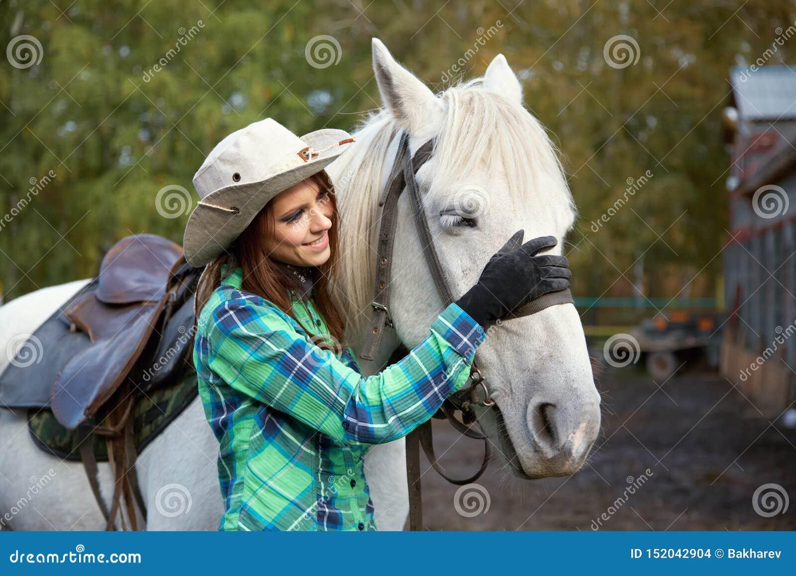 Nettes lächelndes Cowgirl mit einem Schimmel