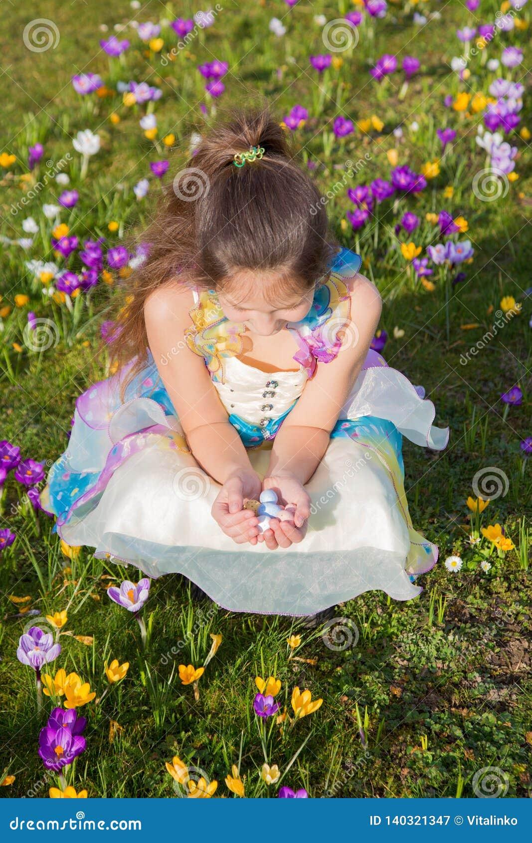 Nettes lächelndes Kind, das Schokolade Ostereier hält
