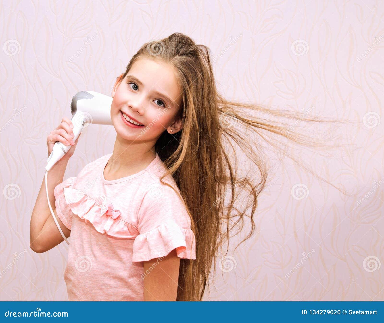 Nettes lächelndes Kind des kleinen Mädchens, das ihr langes Haar mit Haartrockner trocknet