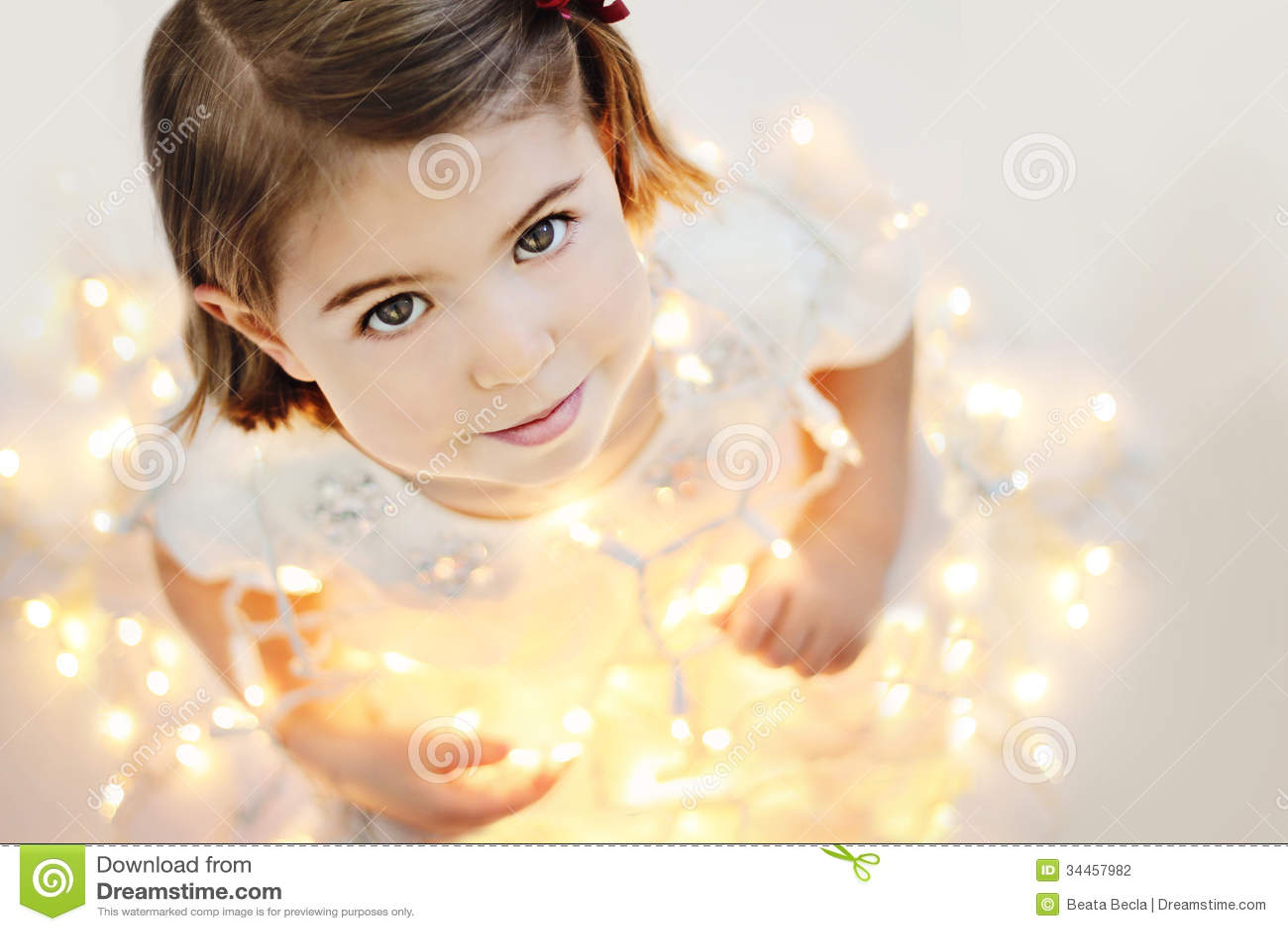 Nettes, lächelndes kleines Mädchen mit glühenden Weihnachtslichtern