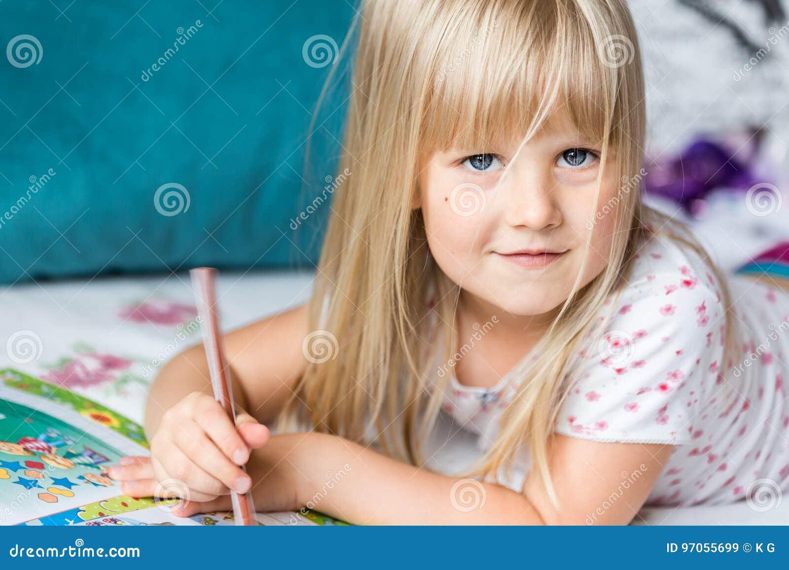 Nettes liitle blondes Mädchen, das auf einem Bett liegt und Hausarbeit macht