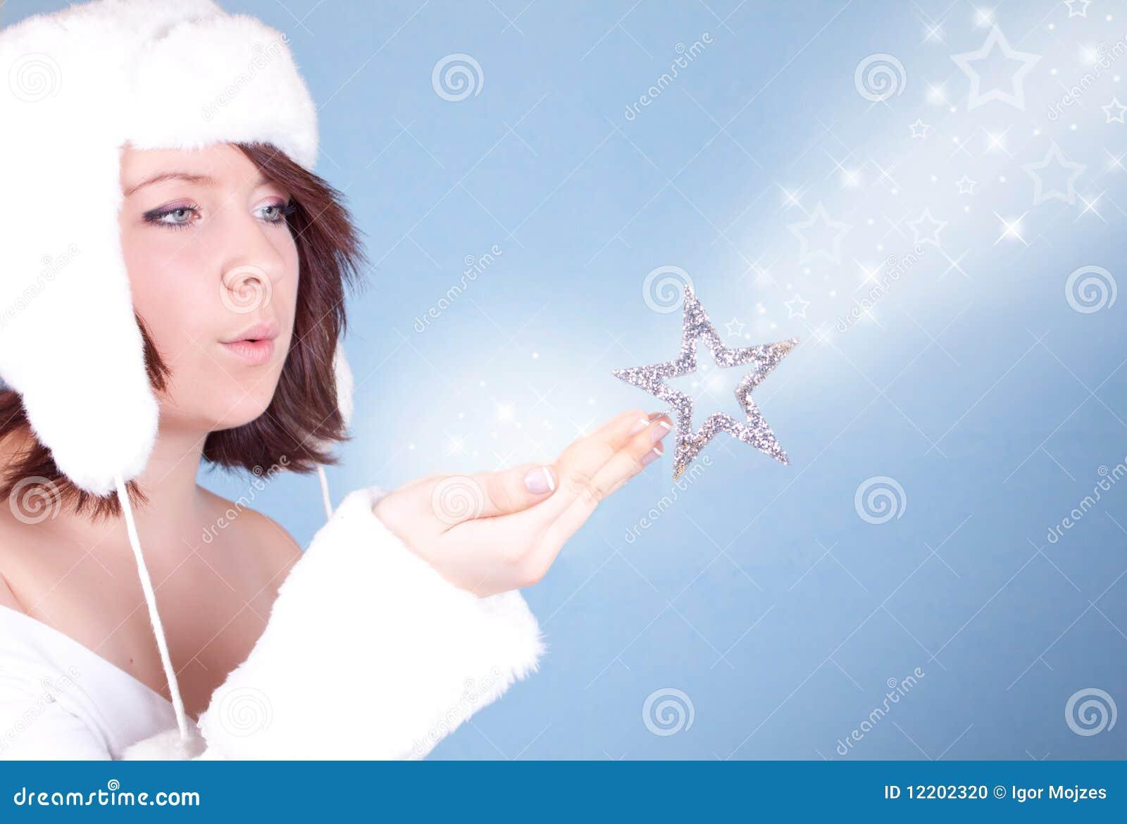Nettes Mädchen im weißen Hut, der einen Schnee durchbrennt