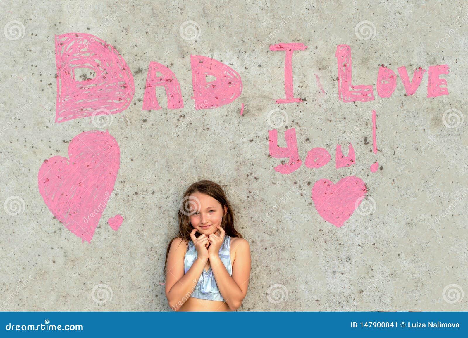 Nettes M?dchen, das ich liebe dich auf dem Hintergrund der Wand mit dem W?rter Vati l?chelt Konzept des gl?cklichen Vatertags