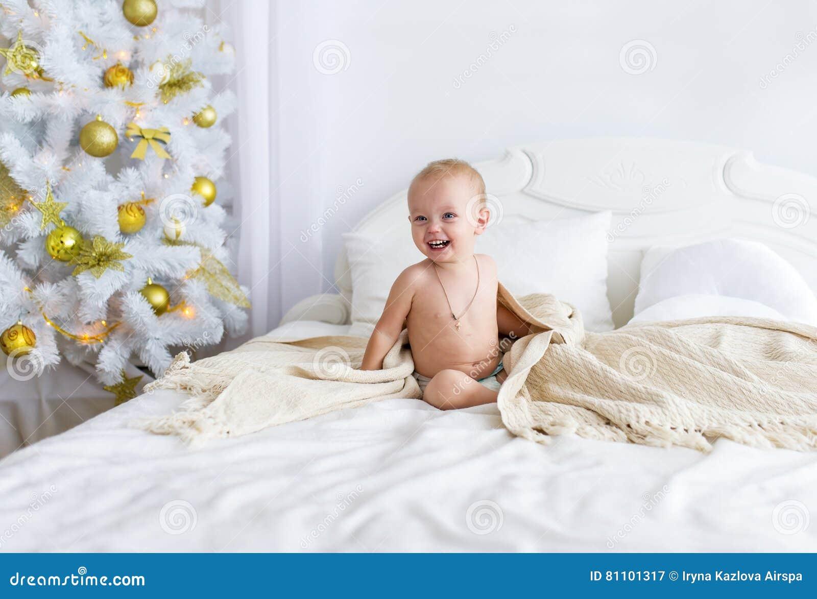 nettes nacktes baby, das auf bett am schlafzimmer sitzt, Schlafzimmer