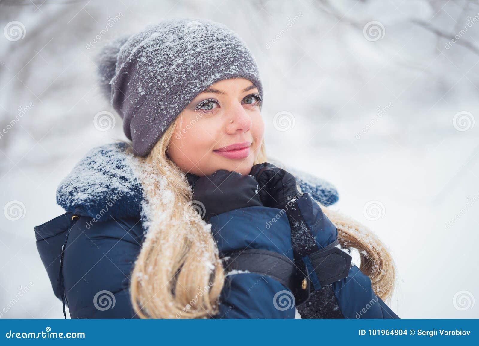 Nettes Porträt der jungen Frau, das mit Schnee im warmen woolen Hut und im Mantel im Winterpark spielt