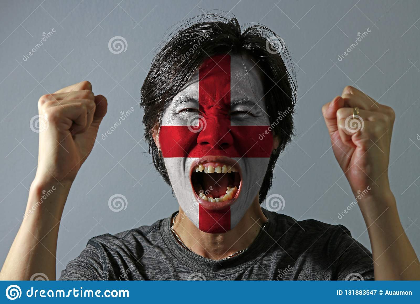 Nettes Porträt eines Mannes mit der Flagge des Englands malte auf seinem Gesicht auf grauem Hintergrund