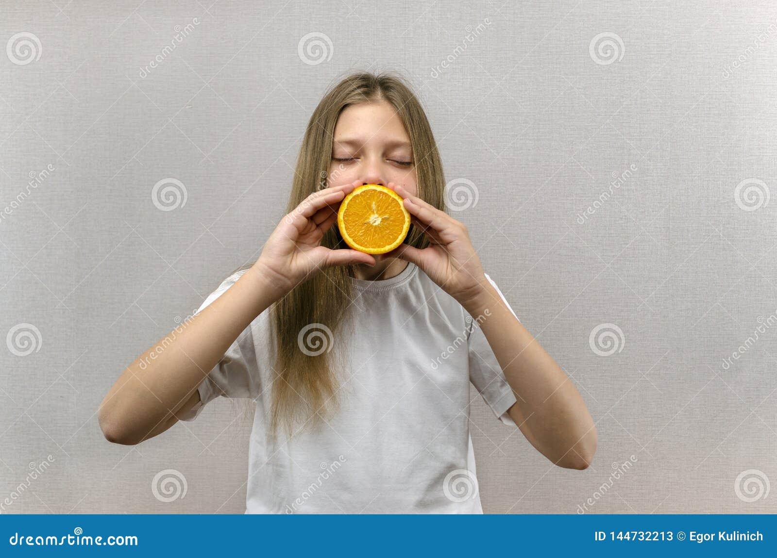 Nettes sch?nes M?dchen h?lt zur H?lfte von orange H?lften Positive Gef?hle Gesunde Nahrung Veggie und strenger Vegetarier