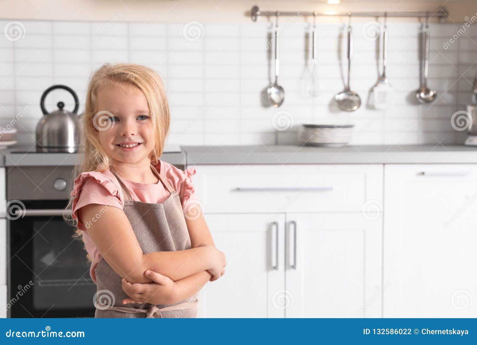 Nettes tragendes Schutzblech des kleinen Mädchens nahe Ofen in der Küche