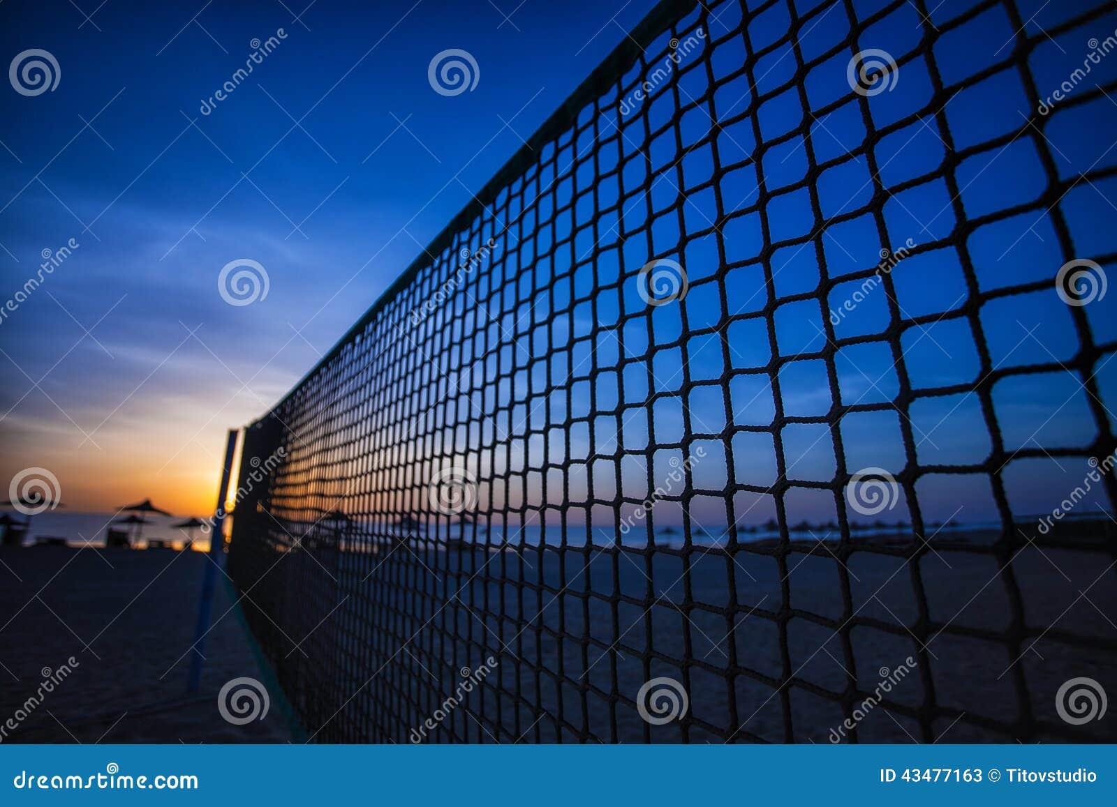 Netto volleyboll och soluppgång på stranden