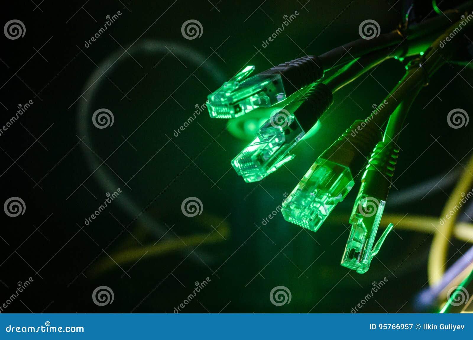 Netwerkschakelaar en ethernet kabels, symbool van globale mededelingen Gekleurde netwerkkabels op donkere achtergrond met lichten