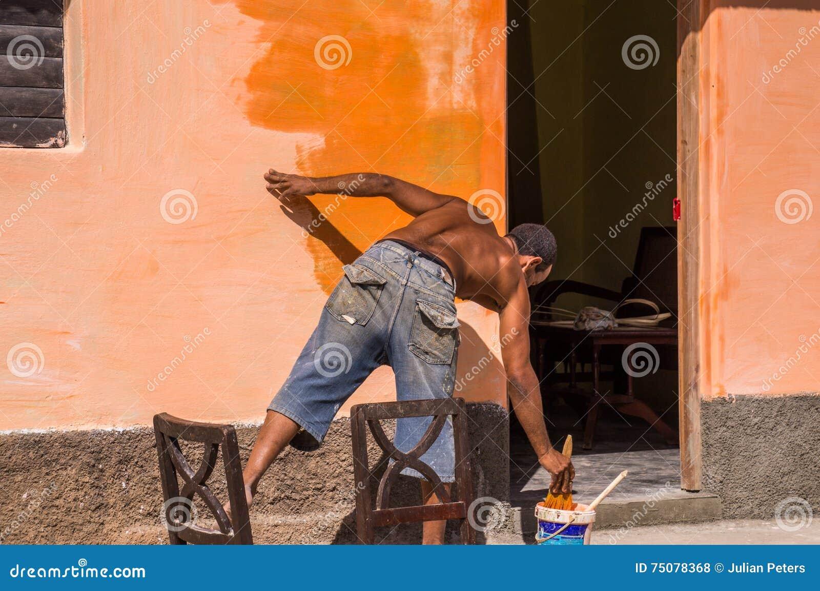 Neu streichen von Kuba: Mann, der orange Wand malt