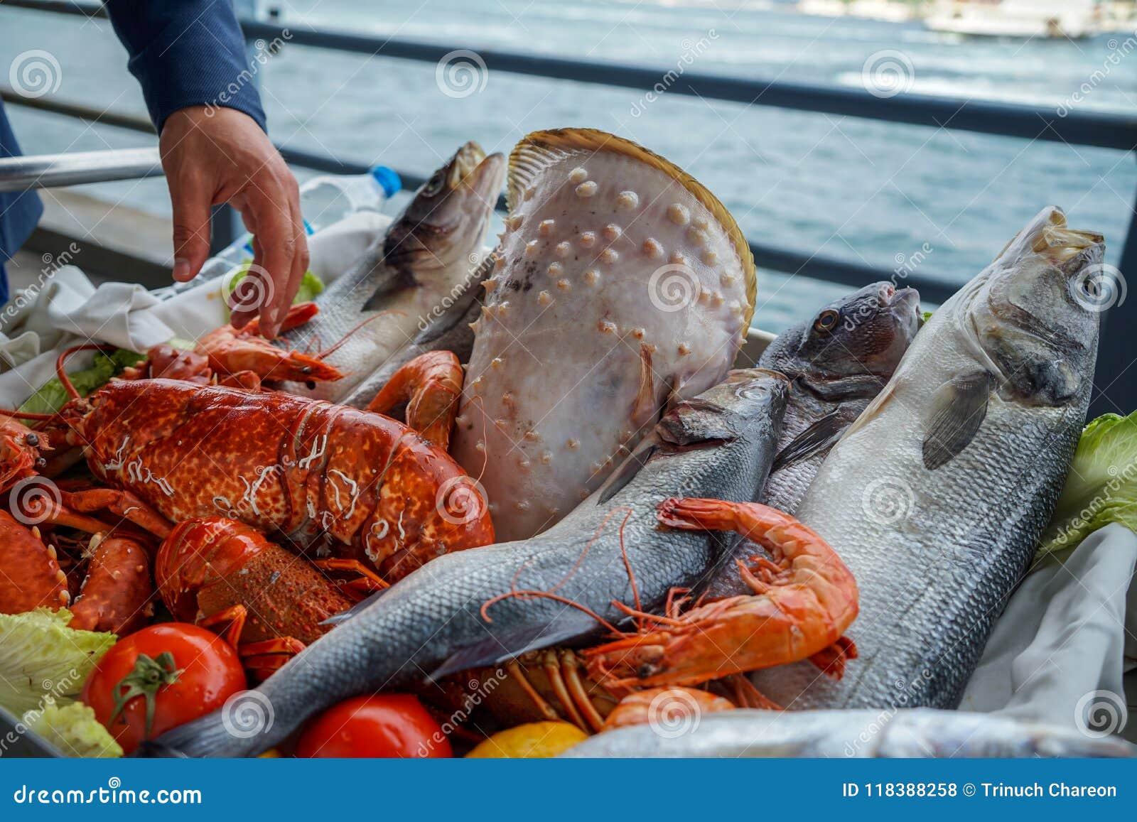 Neue Darstellung der rohen Meeresfrüchte auf Warenkorb am Küstenrestaurant mit einer Mannhand einschließlich Fische, Garnele, Obe
