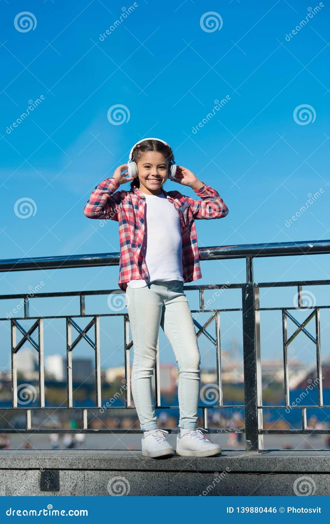 Neue Musikarten zu entdecken ist große Weise in Kultur Mädchenkind hören Musik draußen mit modernen Kopfhörern zicklein