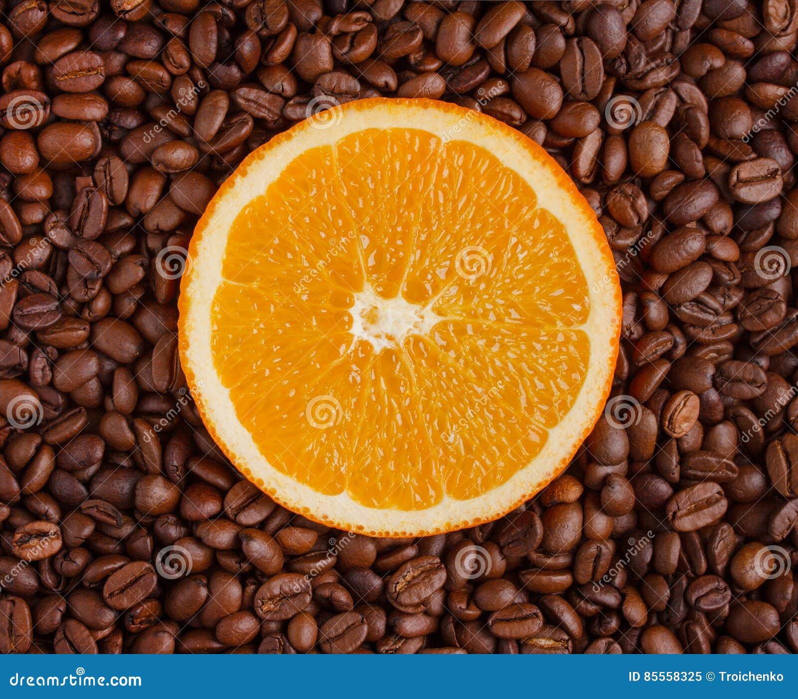 Neue Scheibe der Orange auf einem Hintergrund von Kaffeebohnen