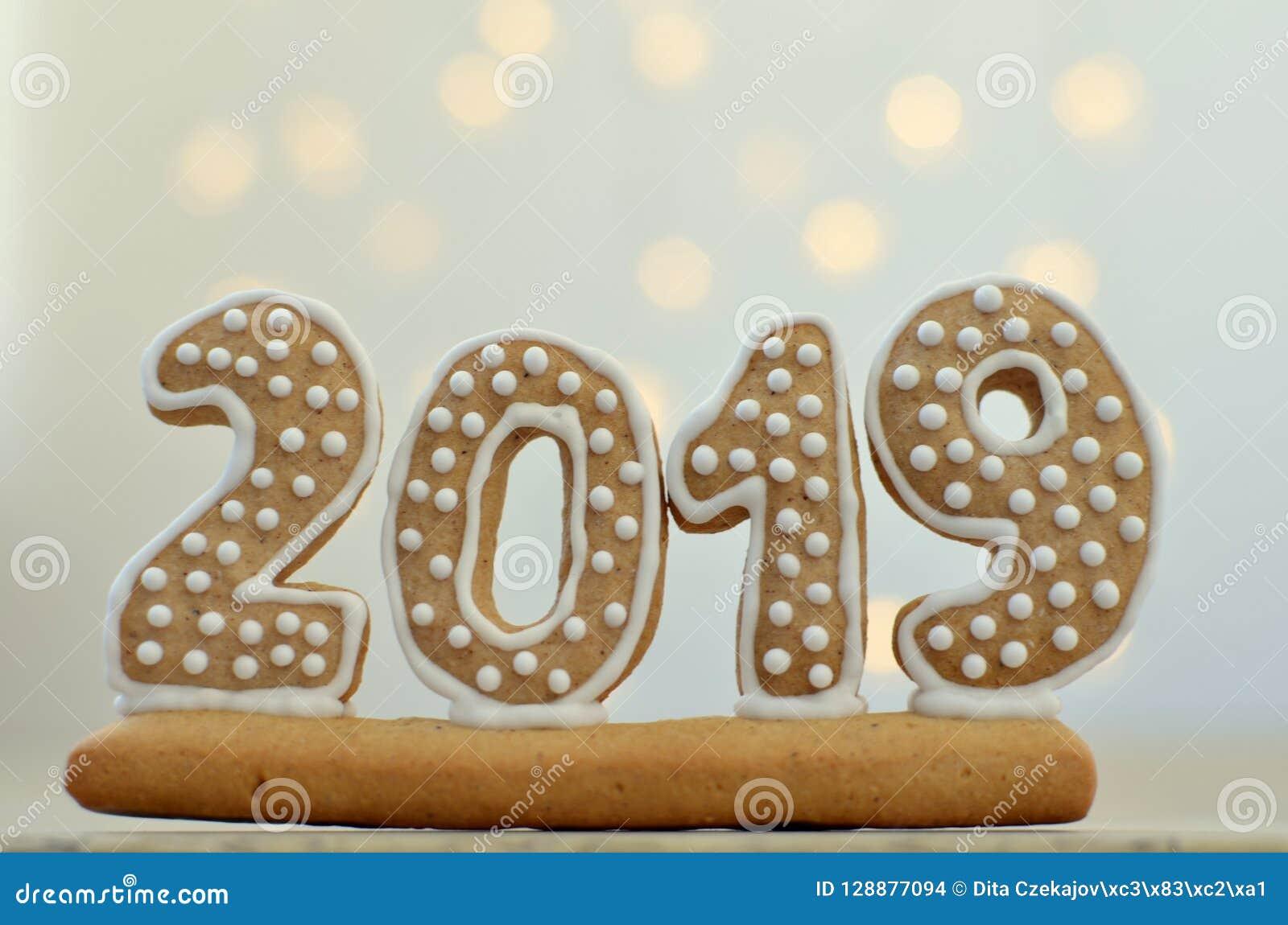 Neues Jahr 2019 Lebkuchenzahlen auf einem hölzernen Brett Weihnachtslichter auf dem Hintergrund Grüße des neuen Jahres Passend al