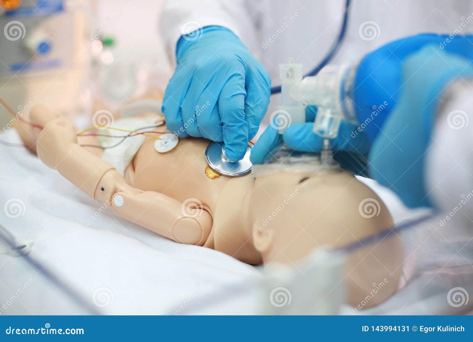 Neugeborene Wiederbelebung Endotracheal Intubation Übende medizinische Fähigkeiten auf einer medizinischen Attrappe Medizinische