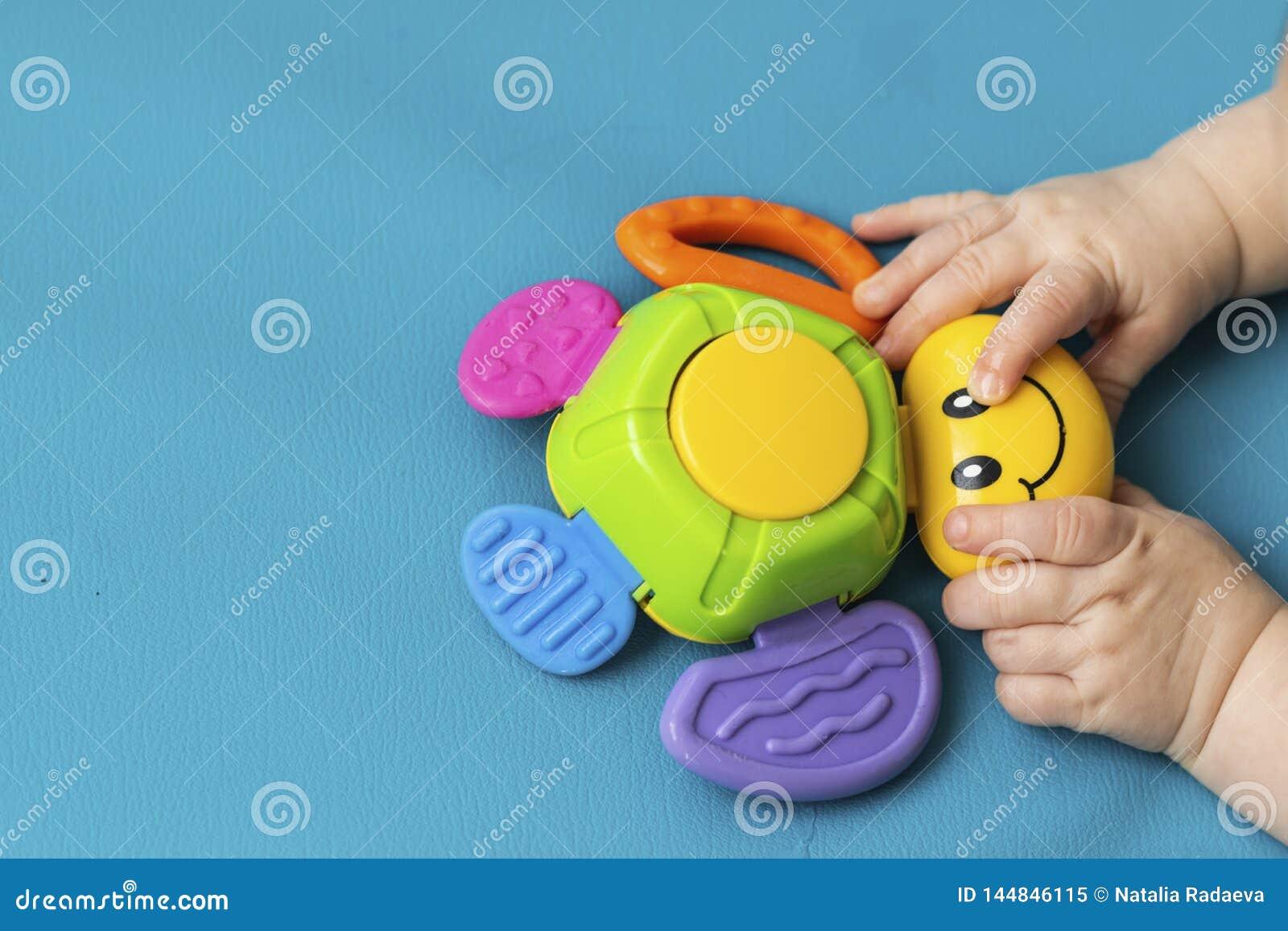 Neugeborener Griff des Kleinkindes kleine Handeine Spielzeugwanze mit einem L?cheln auf einem blauen Hintergrund aquamarin Nahauf
