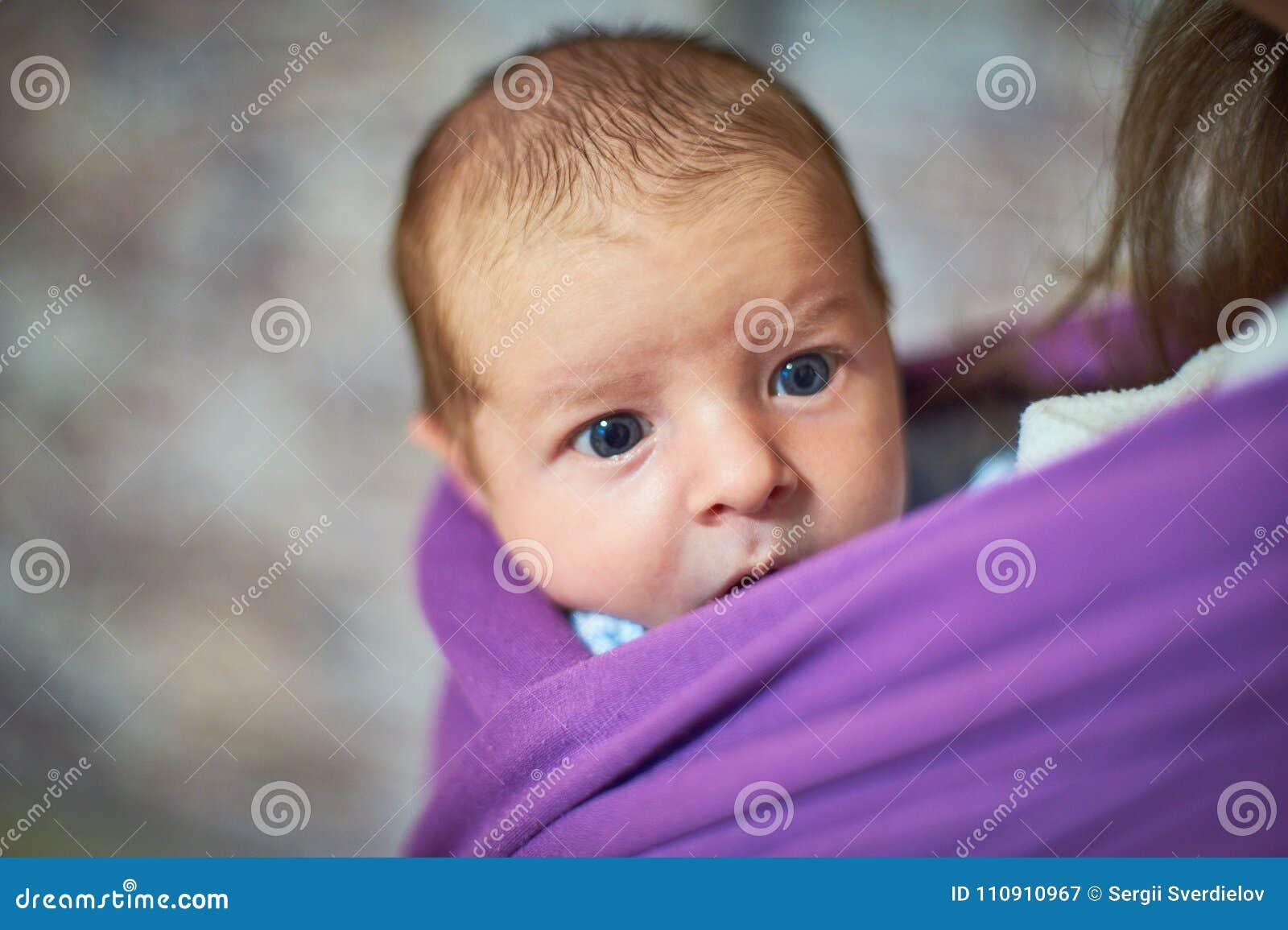 Neugeborenes Kinderbaby in einem Riemen