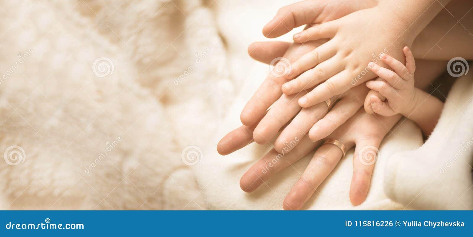 Neugeborenes Kinderhand Nahaufnahme der Schätzchenhand in Muttergesellschafthände Familien-, Mutterschafts- und Geburtskonzept fa