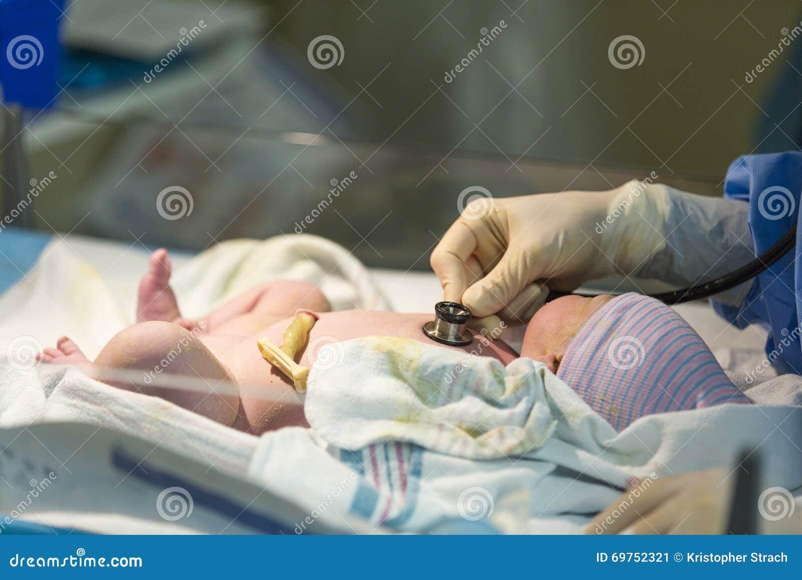 Neugeborenes männliches Baby, das mit Stethoskop überprüft wird