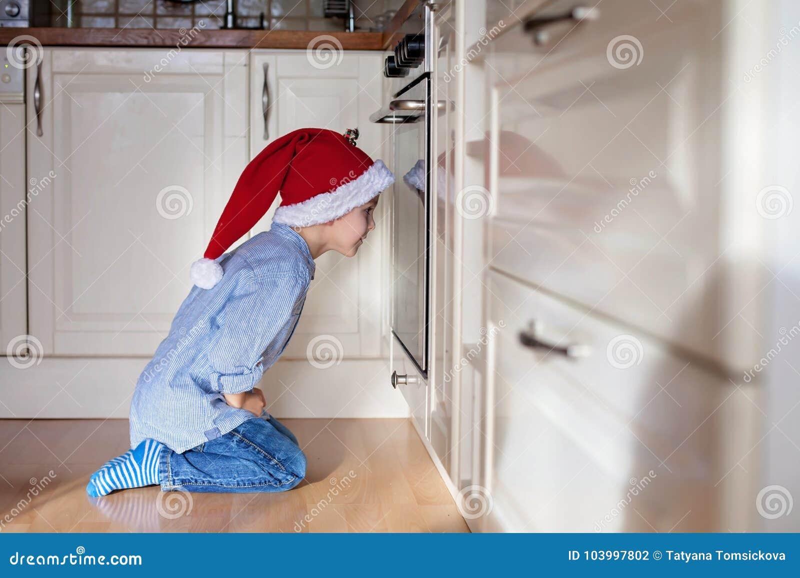Neugieriger kleiner Junge, aufpassender Ingwer Plätzchen im Ofen panieren