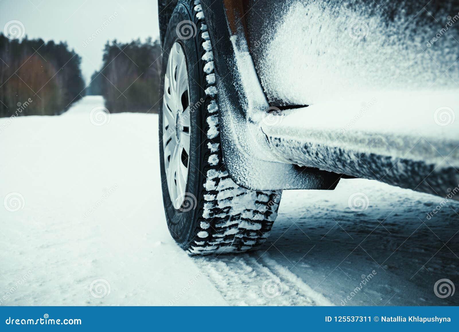 Neumáticos de coche cubiertos con nieve en el camino del invierno