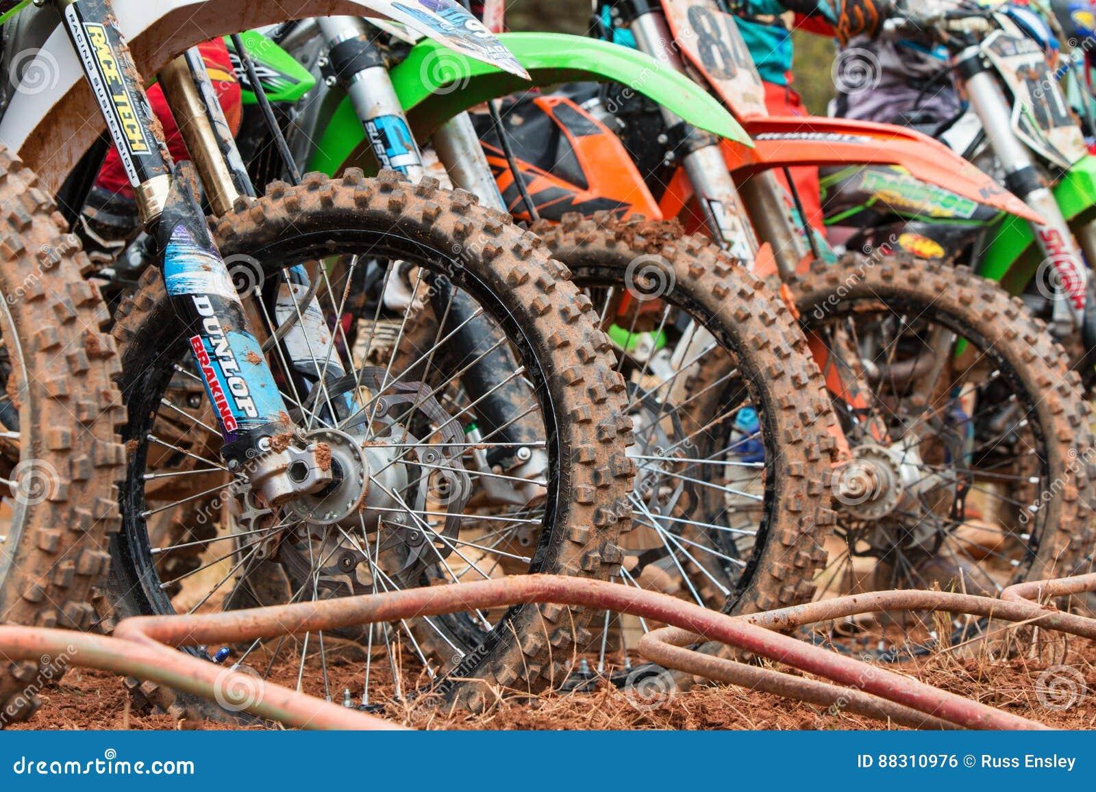 Neumáticos de la bici de la suciedad alineados en el comienzo de la raza del motocrós