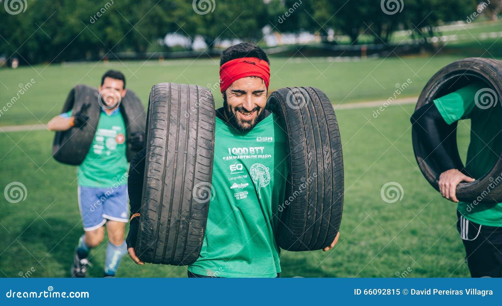 Neumáticos que llevan del corredor en una prueba de la raza de obstáculo extrema