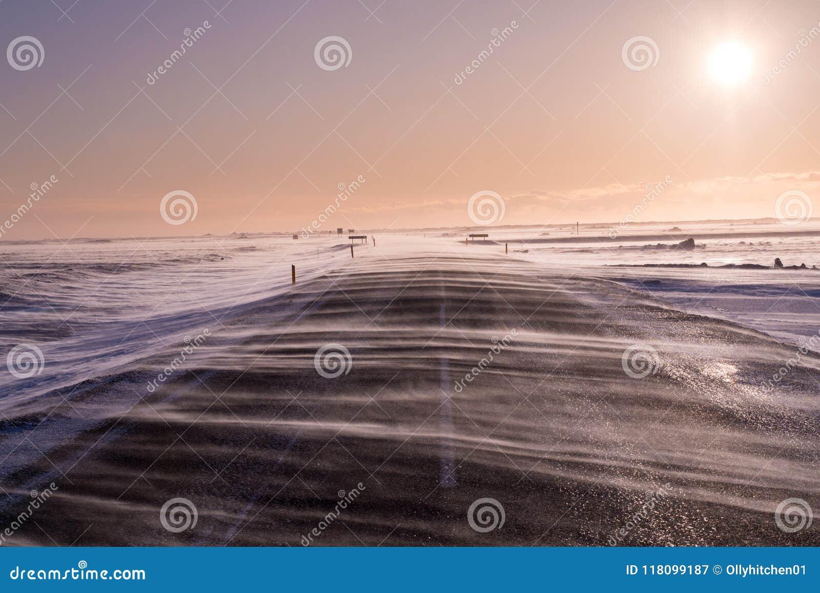 A neve de condução flui através da estrada, obscurecendo quase o durante ventos pesados em Islândia do sul