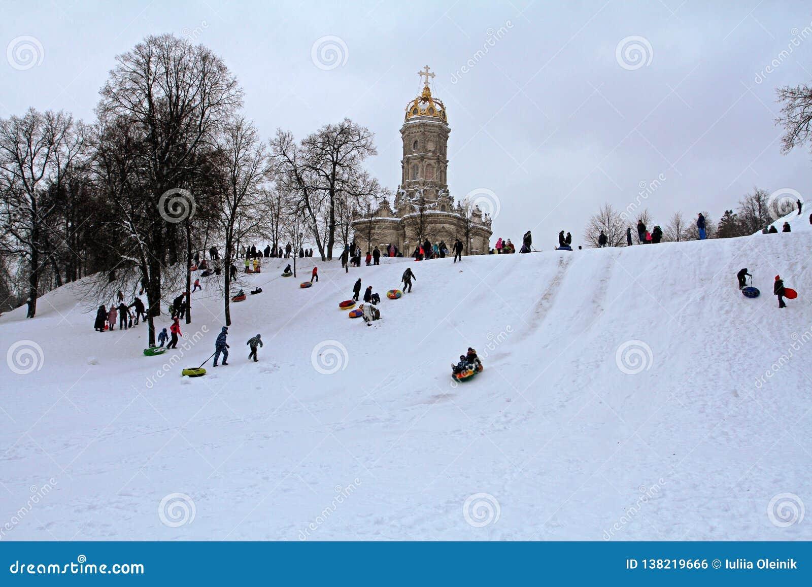 Neve-tubulação dos povos no parque do inverno na vila de Dubrovitsy perto de Podolsk