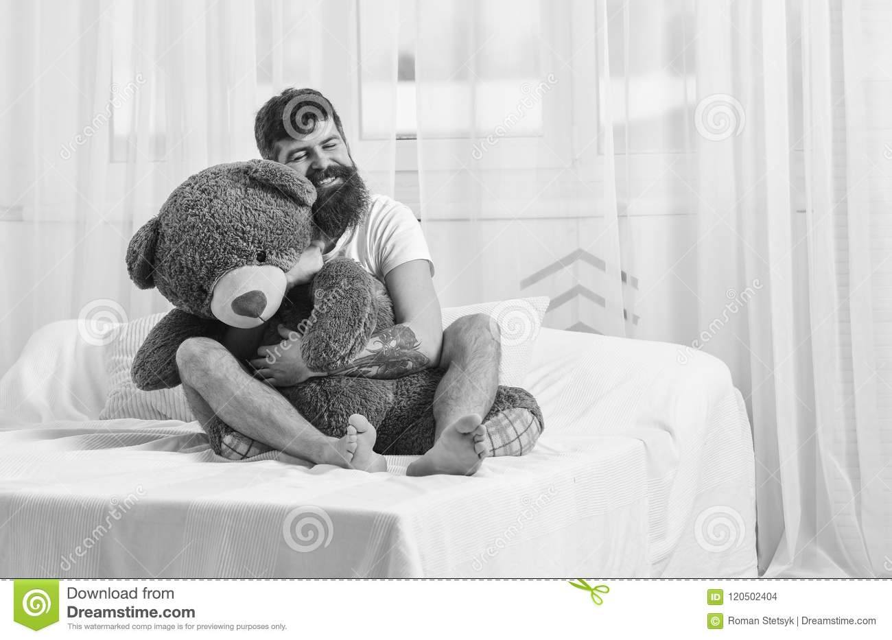 Never grow up concept. Guy on happy face hugs giant teddy bear. Man sits on bed and hugs big toy, white curtains on