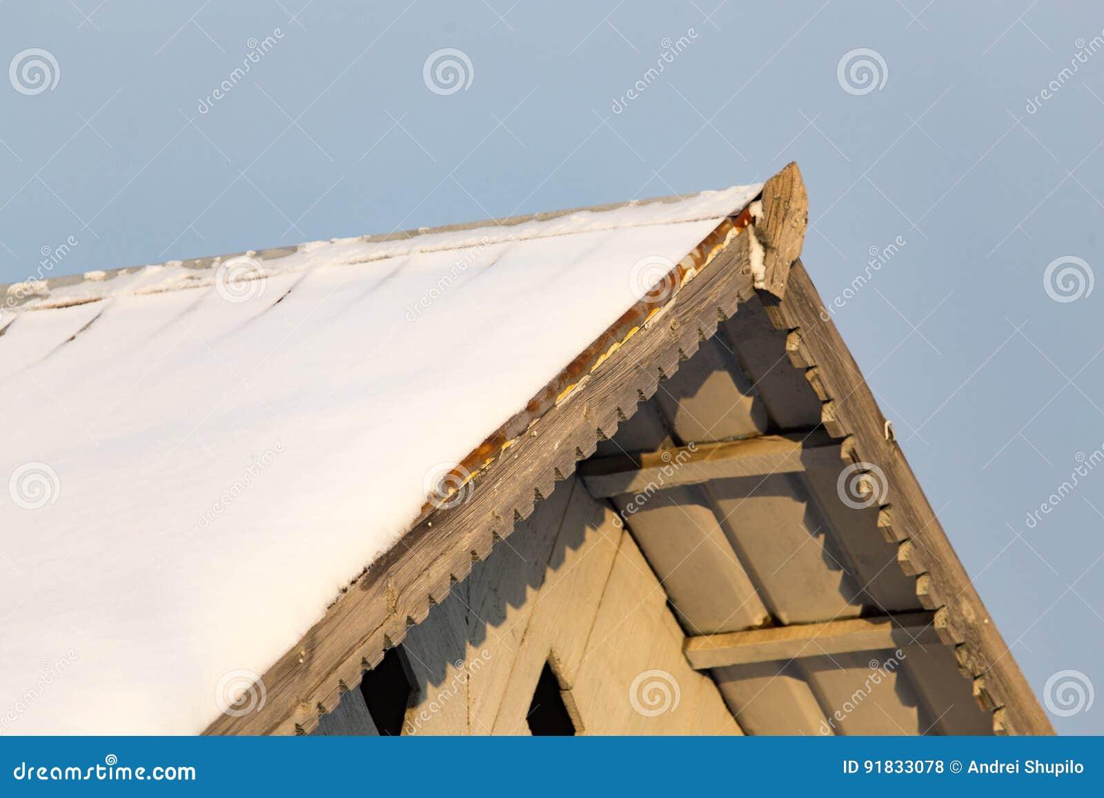 Nevichi sul tetto della casa al tramonto