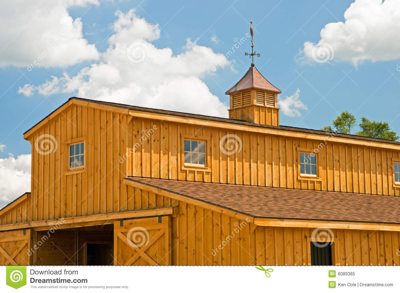 view of a new wooden farm barn with weather vane on top of a cupola.