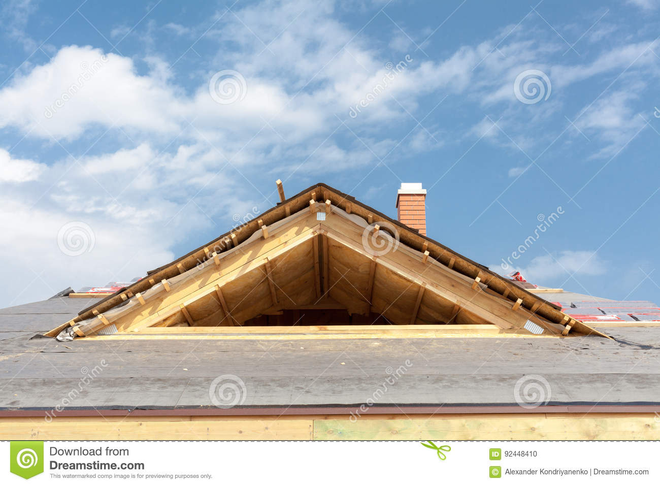 New frame house under construction. Roof with asphalt shingles, chimney and insulation material.