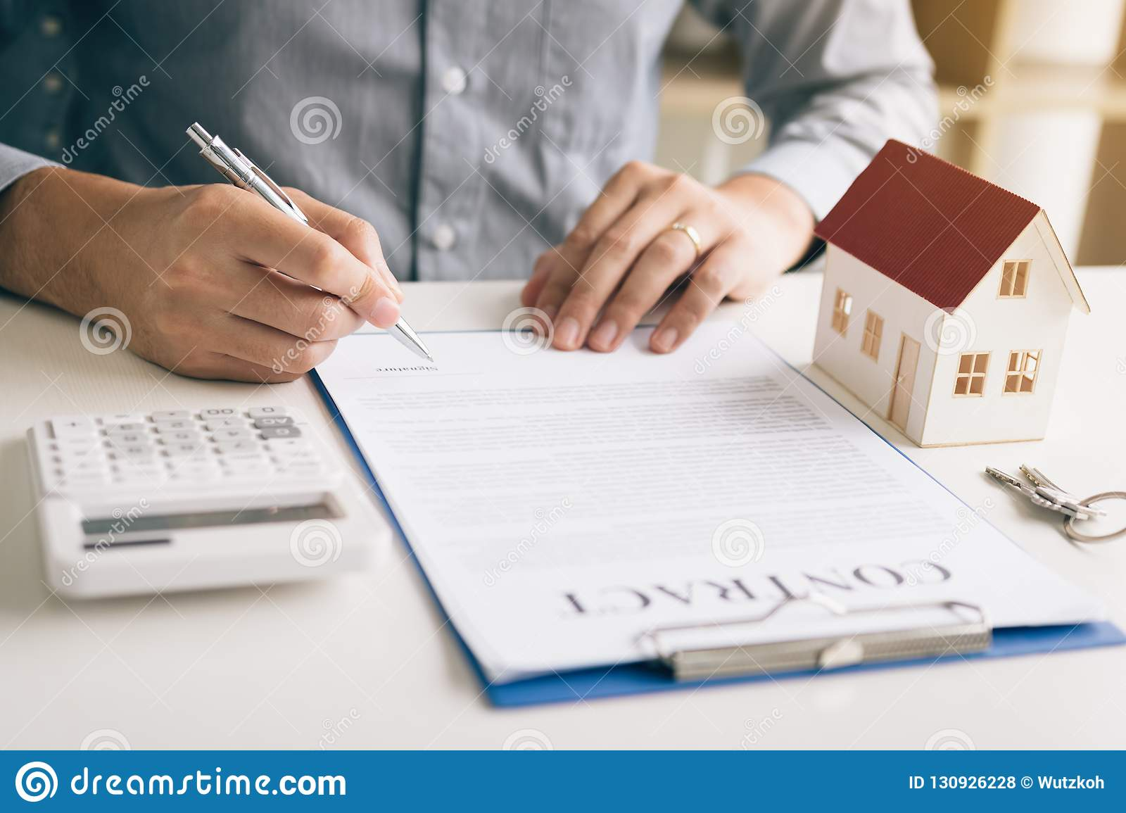 New home buyer signing contract on desk in office room.
