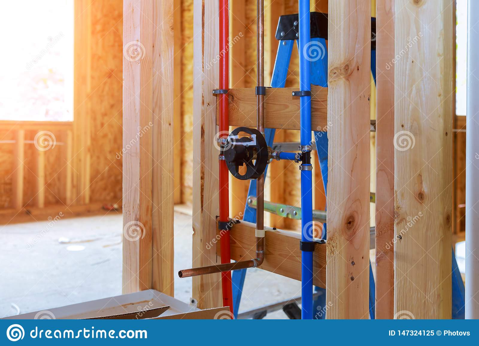 New home plumbing inside a house frame under construction interior