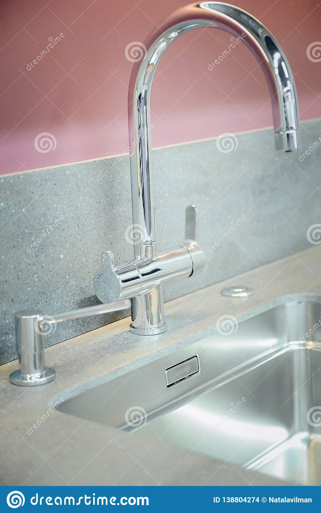 A new kitchen sink with an artificial stone countertop. The concept of modern kitchen interior. Vertical photography. Closeup,