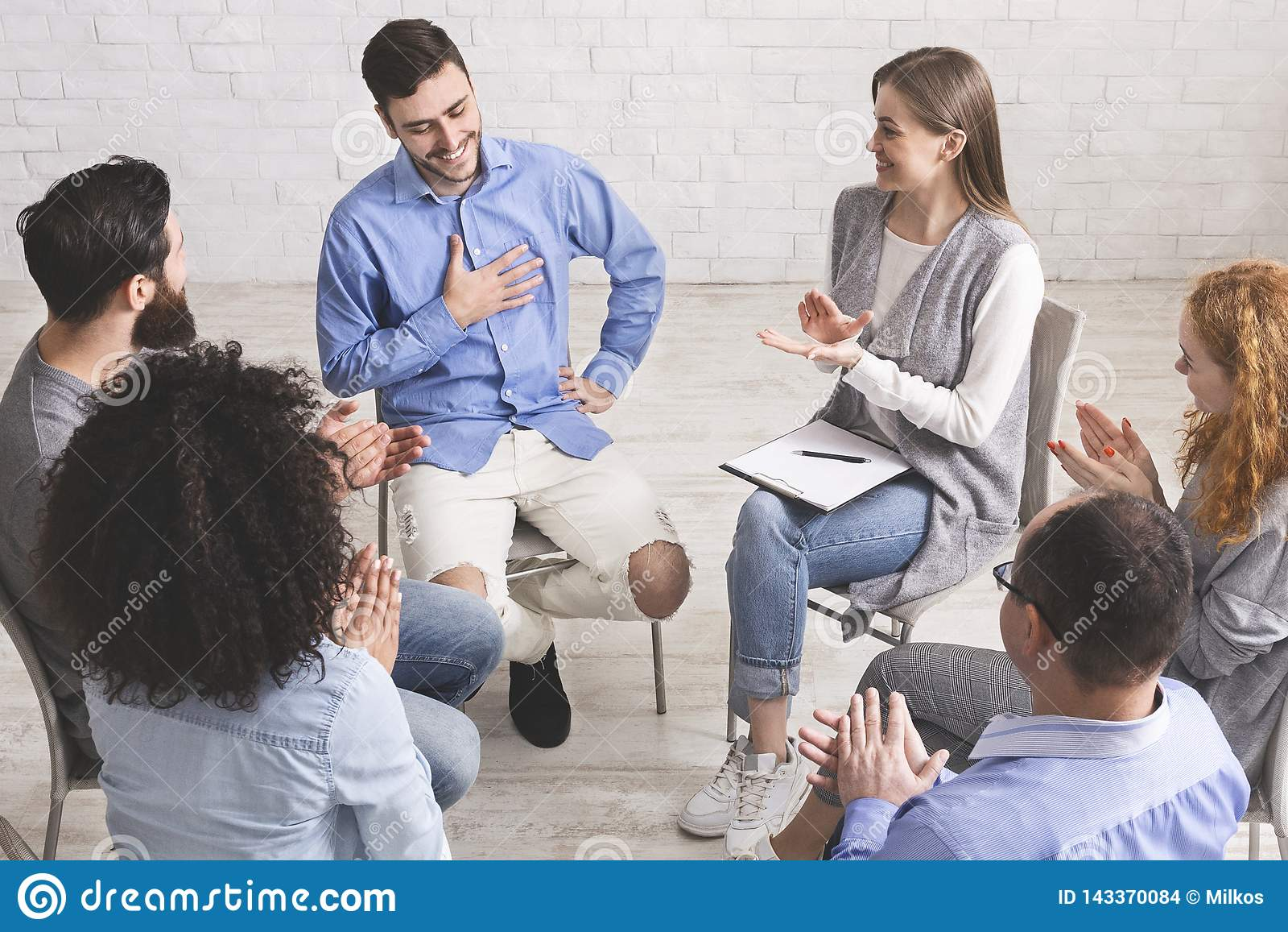 Happy people clapping at support group meeting