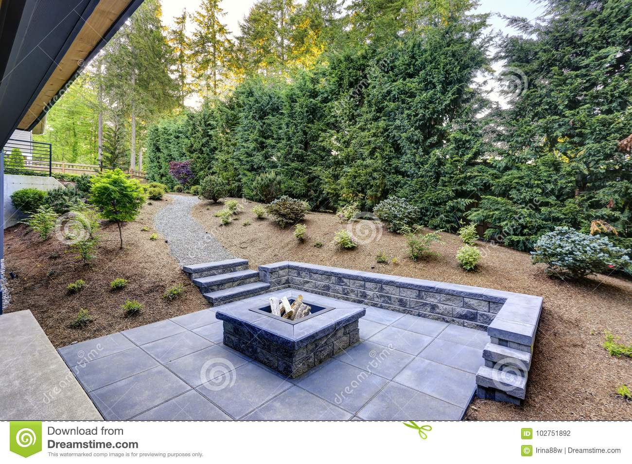 New Modern Home Features A Backyard With Fire Pit Stock Photo
