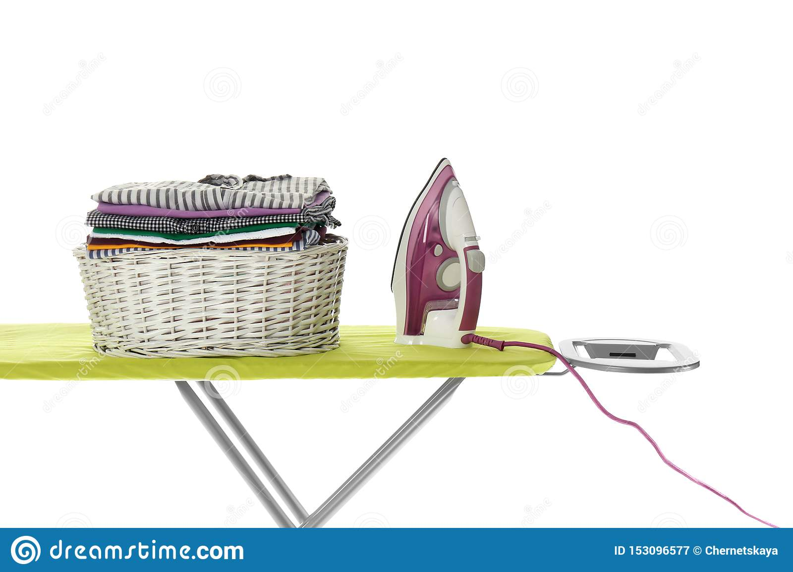 New modern iron and basket with clean laundry on board