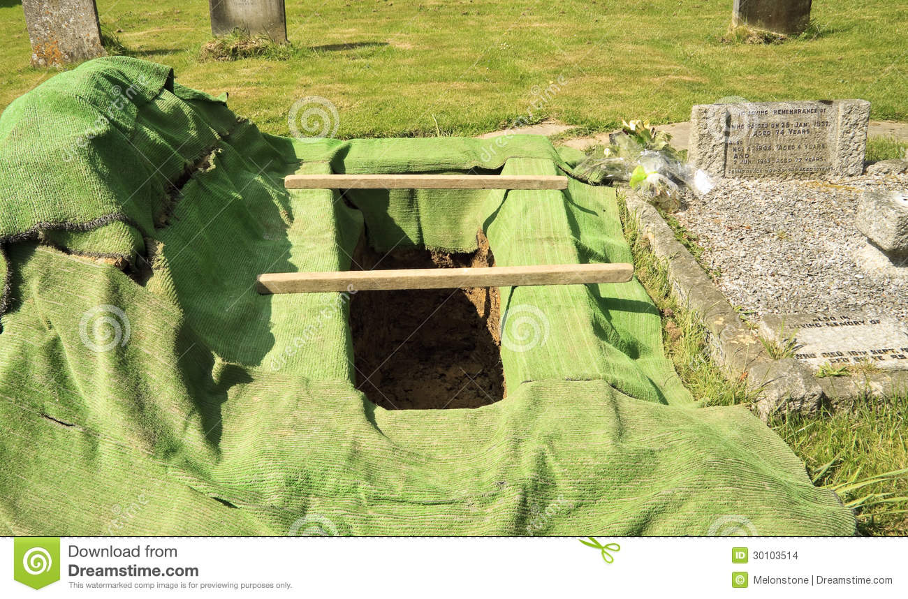 new open grave prepared for a funeral burial service in a graveyard.