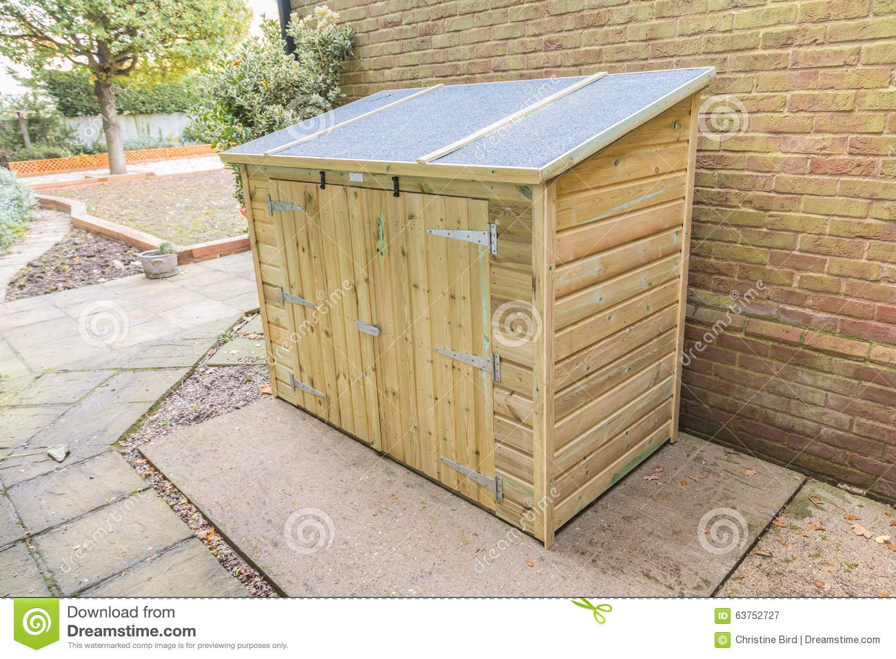 New Tool Shed In A Garden On A Patio By A Brick Wall With A Sloping Roof.